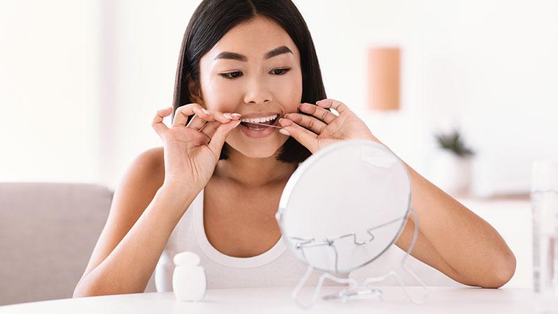 Woman Flossing Teeth | Flossing and Brushing Dentist Kalamazoo, MI | Karen Mitchell Dentistry